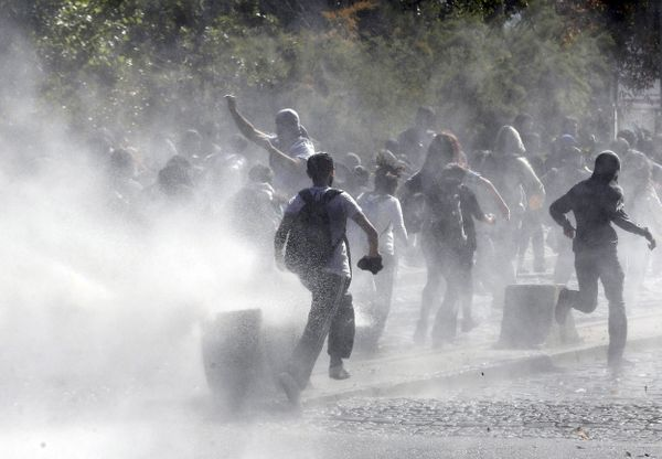 Demonstrators run a water cannon as they clash with riot police outside of the Middle Eastern Technical University (METU) in