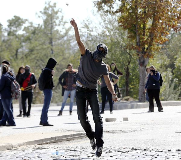 A demonstrator throws a stone at anti-riot police during clashed outside of the Middle Eastern Technical University (METU) in