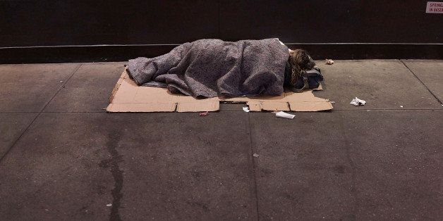 NEW YORK, NY - AUGUST 22:  A homeless person sleeps on a Manhattan street on August 22, 2014 in New York City. According to t