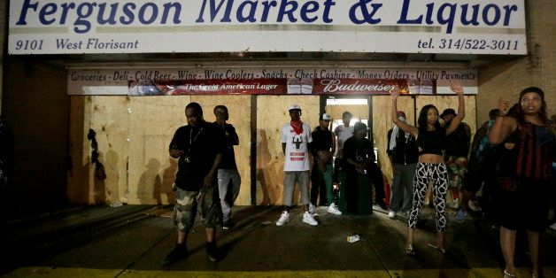 People stand in front of a convenience store after it was looted early Saturday, Aug. 16, 2014, in Ferguson, Mo. The violence