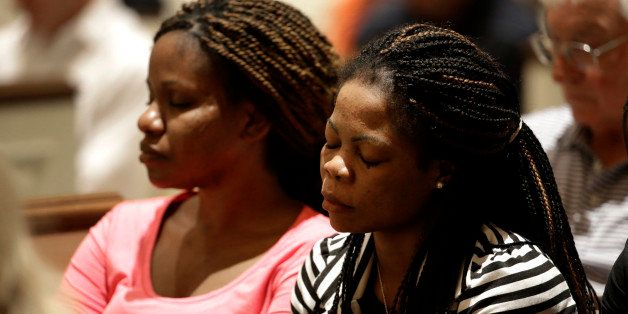 Princess Duo, left, and Mamie Mangoe, right, both natively of Liberia who now live in Dallas, bow their head in prayer during