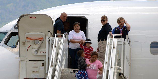 Two women and their children descend for a plane at Palmerola air base in Comayagua, 80 km north of Tegucigalpa on August 11,