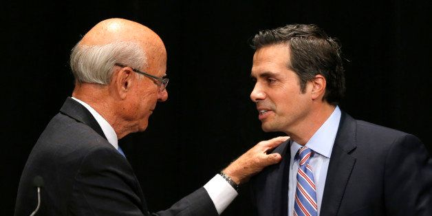 Sen. Pat Roberts, R-Kan., left, greets independent candidate Greg Orman, right, before a debate in Overland Park, Kan., Wedne
