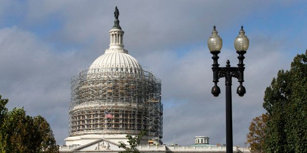 Scaffolding begins to obscure the Capitol Dome in Washington, Tuesday, Oct. 14, 2014, for a long-term repair project to fix c