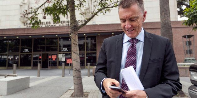 In this June 10, 2014, photo, Los Angeles Unified School District Superintendent John Deasy checks his phone outside the Stan