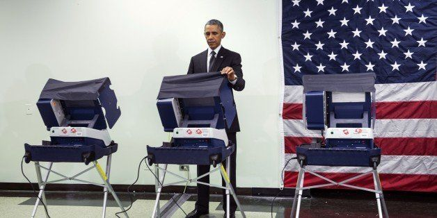 US President Barack Obama casts an electronic ballot while participating in early voting October 20, 2014 in Chicago, Illinois. While campaigning and fundraising for Democrats, Obama took the opportunity to early vote in the 2014 US midterm elections. AFP PHOTO/Brendan SMIALOWSKI (Photo credit should read BRENDAN SMIALOWSKI/AFP/Getty Images)