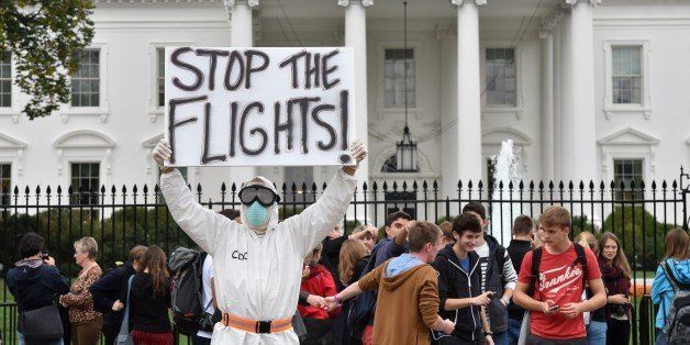 Jeff Hulbert from Annapolis, Maryland, dressed in a protective suit and mask holds a poster demanding for a halt of all fligh