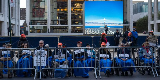 """People, some in wheelchairs, gather at Lincoln Center, with the Metropolitan Opera House in the background, as they protest """""""