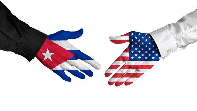 Diplomatic handshake between leaders from Cuba and the United States with flag-painted hands.
