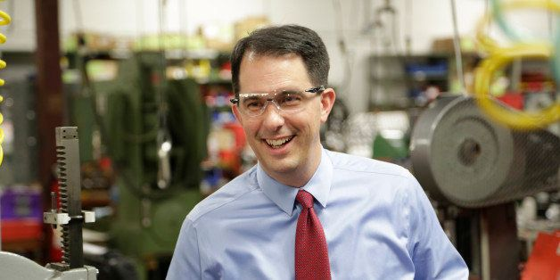In this Sept. 23, 2014 photo Wisconsin Repubican Gov. Scott Walker makes a re-election campaign stop at a small business in R