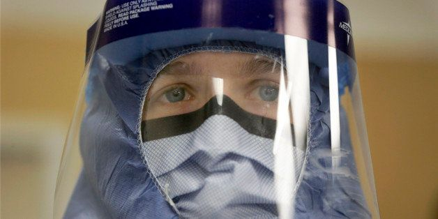 FILE - In this Oct. 16, 2014, file photo, Registered nurse Keene Roadman, stands fully dressed in personal protective equipme