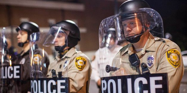 FERGUSON, MO - OCTOBER 11:  St. Louis County Police Officers stand guard in front of the Ferguson Police Department during a