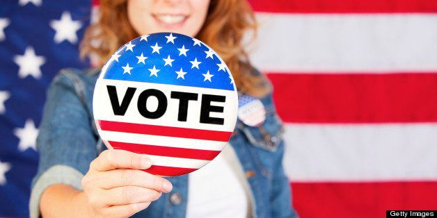 Young woman holding a large vote pin.