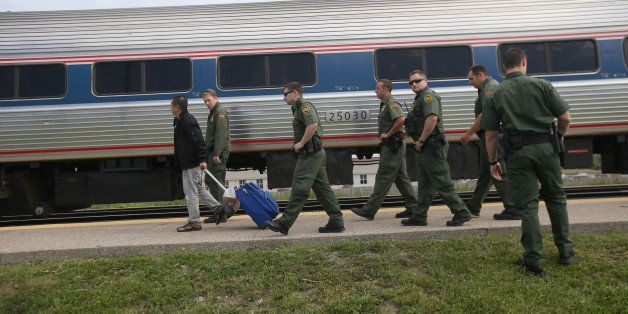 DEPEW, NY - JUNE 05:  U.S. Border Patrol agents escort an individual without identification after checking for undocumented i