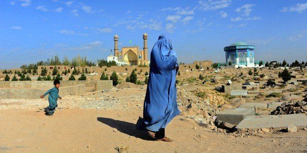 A  burqa clad-Afghan woman walks near a cemetery in Herat province on October 12, 2014. Afghanistan's economy has improved si