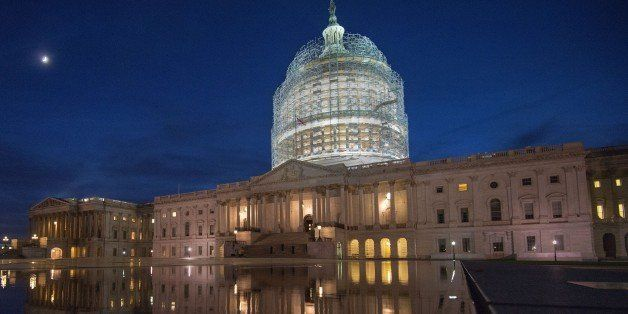 The US Capitol in scaffolding is reflected in a water pool on October 28, 2014 in Washington, DC.  The US Capitol dome will u