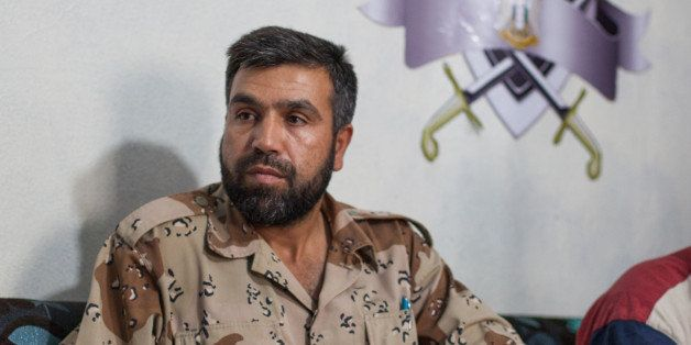 Jamal Maarouf, commander of the Free Syrian Army's Syrian Martyrs' Brigade, listens to a question during an interview with jo
