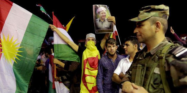 In this Tuesday, Oct. 28, 2014 photo, a supporter of Kurdish Peshmerga forces holds a large Kurdish flag and a poster of Iraq