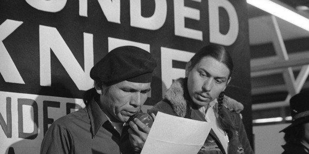 File - In this March 18, 1973 file photo taken in Wounded Knee, S.D., American Indian Movement leader Dennis Banks, left, rea