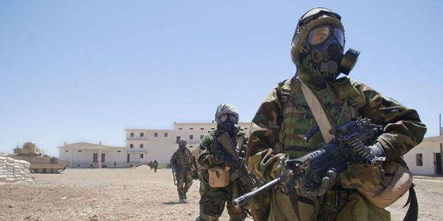 US Army soldiers from 2-8 Infantry, 2nd Brigade, 4th Infantry Division wearing their full chemical protection suits walk insi