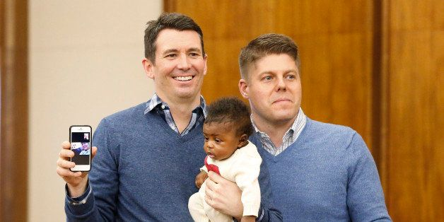 Jim, left, and Jason Shaffer, hold their daughter Norah, 3 mo., while being married in a group by the Oakland County Clerk in