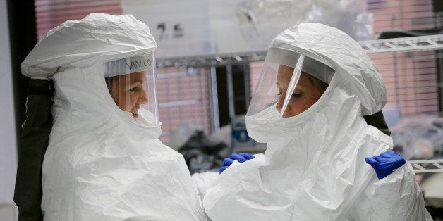 FILE- In this Oct. 24, 2014, file photo, members of the Department of Defense's Ebola Military Medical Support Team assist ea