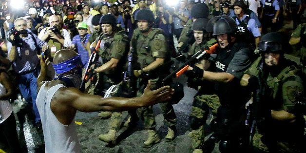FILE - In this Aug. 20, 2014 file photo police arrest a man as they disperse a protest against the shooting of Michael Brown