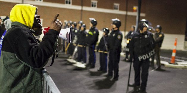 FERGUSON, UNITED STATES -  NOVEMBER 20: Protestors yell at a line of Police Officers at the Ferguson Police Department during