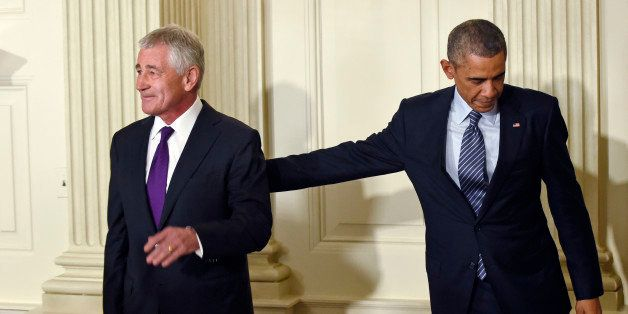 President Barack Obama, left, reaches over to touch Defense Secretary Chuck Hagel, left, following an announcement of Hagel's