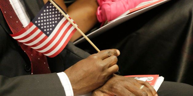 A new United States citizens holds an American flag during a naturalization ceremony, Wednesday, July 9, 2014 in New York. De