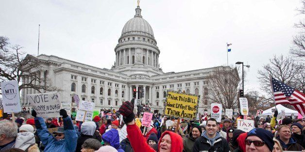 Protesters march outside the state Capitol Saturday, March 12, 2011, in Madison, Wis. While Gov. Scott Walker has already sig