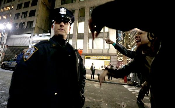 A woman, right, yells at a New York City Police officer during a protest after it was announced that the police officer invol