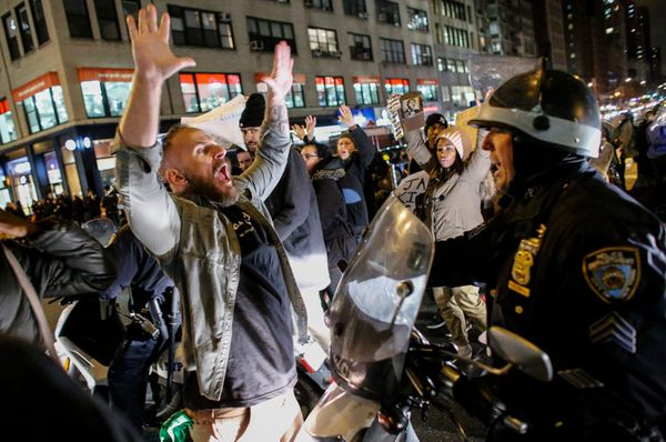 A man yells at a police officer as he takes part during a protest on 6th Avenue in Manhattan after a grand jury decided not t