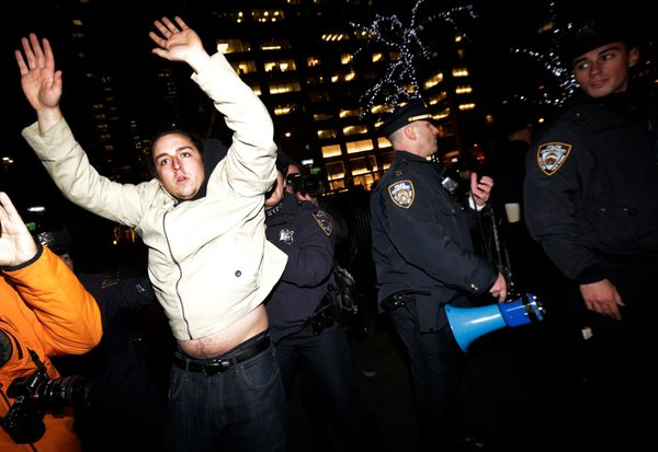 A man, left, holds his hands up as New York City Police officers secure a street near Rockefeller Center during a protest aft