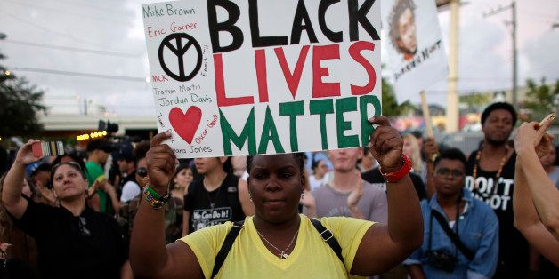 """Desiree Griffiths, 31, of Miami, holds up a sign saying """"Black Lives Matter"""", with the names of Michael Brown and Eric Garner"""