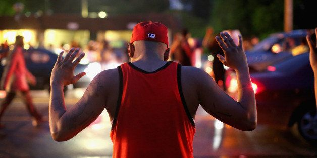 FERGUSON, MO - AUGUST 15:  Demonstrators gather along West Florissant Avenue to protest the shooting of Michael Brown on Augu