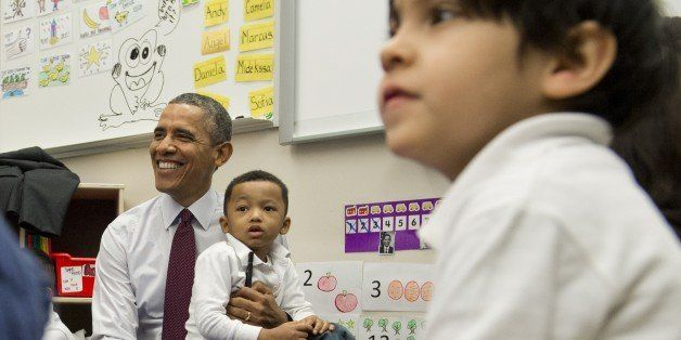 Marcus Wesby sits on the lap of US President Barack Obama as he tours a Pre-K classroom at Powell Elementary School prior to