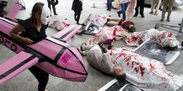 Protestors from Codepink perform mock killings by a woman in a drone costume as they demonstrate the use of military drones by the US goverment outside the Unmanned Systems 2013 exhibition and symposium hosted by The Association for Unmanned Vehicle Systems International (AUVSI) at the Washington Convention Center in Washington, DC, August 13, 2013. The event features more than 8,000 attendees as over 550 exhibitors from around the world display the latest in unmanned systems, robotics and related products, including aerial drones, underwater robots and land-based vehicles, for military, government and commericial use. AFP PHOTO / Saul LOEB (Photo credit should read SAUL LOEB/AFP/Getty Images)