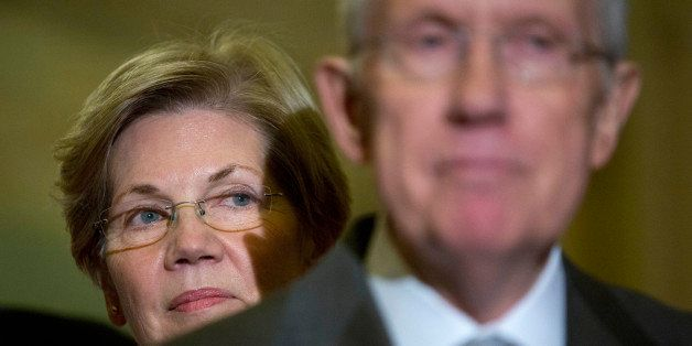 Senator Elizabeth Warren, a Democrat from Massachusetts, left, looks on as Senate Majority Leader Harry Reid, a Democrat from