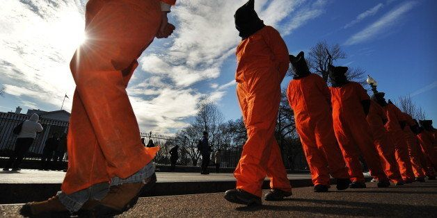 Activists dressed as Guantanamo Bay detainees march during a demonstration organized by Witness Against Torture in front of t