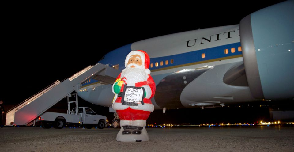"""A Santa figurine with a sign that says """"Hawaii or Bust"""" stands on the tarmac in front of Air Force One before President Barac"""