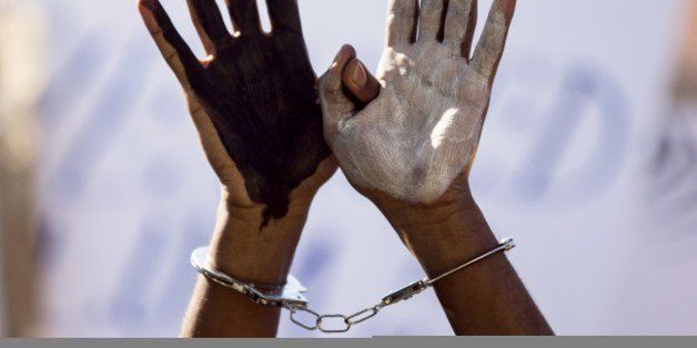 An African asylum seeker, who entered Israel illegally via Egypt, uses handcuffs and raises up his hands painted in black and