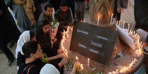 Pakistani civil society activists light candles a day after an attack on an army-run school by Taliban militants in Peshawar