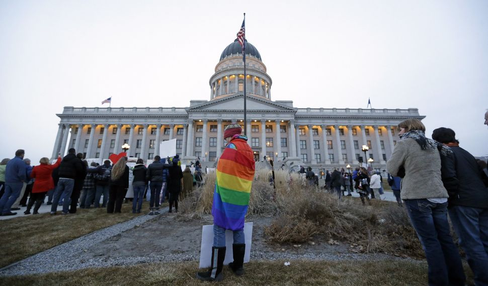 Tiffany Lundeen wears a flag during a rally at the Utah State Capitol, Tuesday, Jan. 28, 2014, in Salt Lake City.