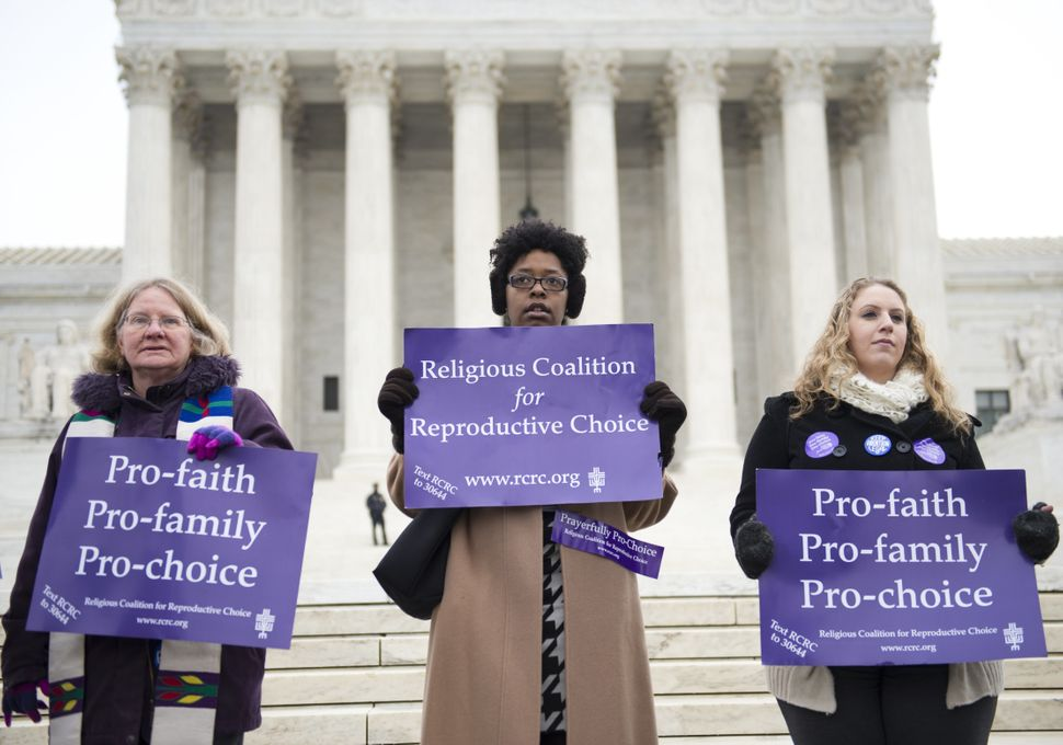 Pro-choice demonstrators stand outside the US Supreme Court following oral arguments in the case of McCullen v. Coakley, deal