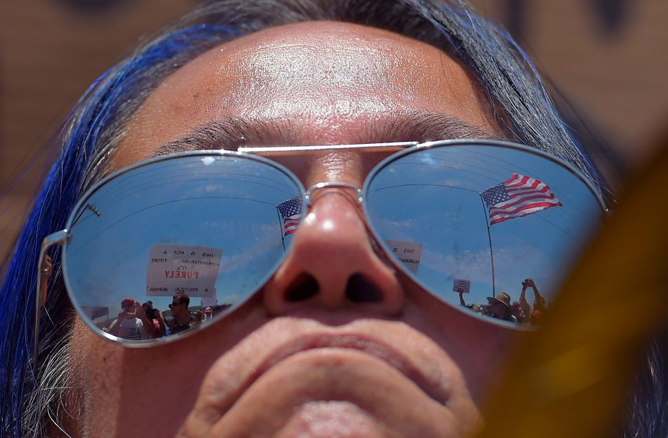 A pro-immigration demonstrator looks across a police line at the opposing side, Friday, July 4, 2014, outside a U.S. Border P