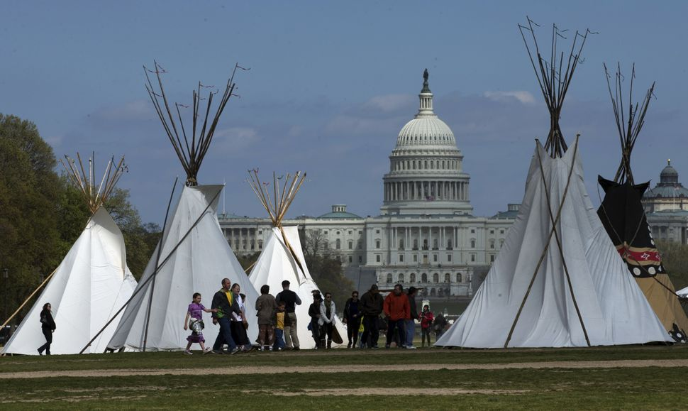 People walk among teepees set up on the National Mall in Washington, Wednesday, April 23, 2014, looking toward the Capitol. T