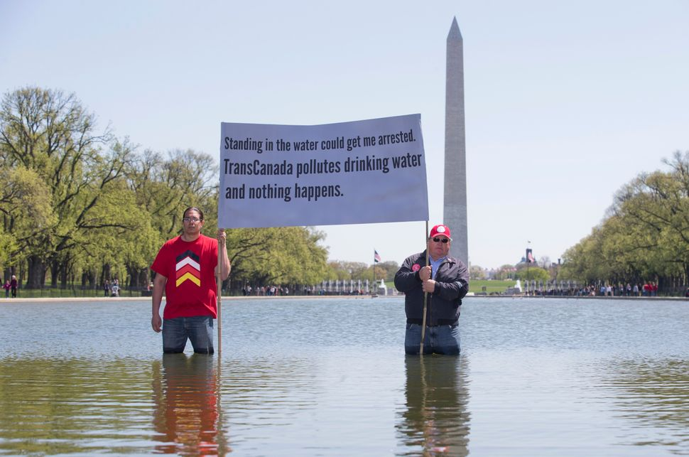 Wizipan Little Elk of the Rosebud Sioux Tribe, left, and farmer Art Tanderup, hold a banner in the reflecting pool on the Nat