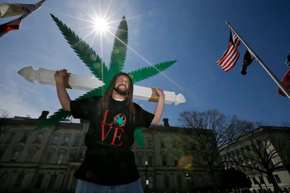 Ed Forchion, a pro-marijuana activist known as NJ Weedman, carries a large cross with huge likeness of a marijuana leaf as he