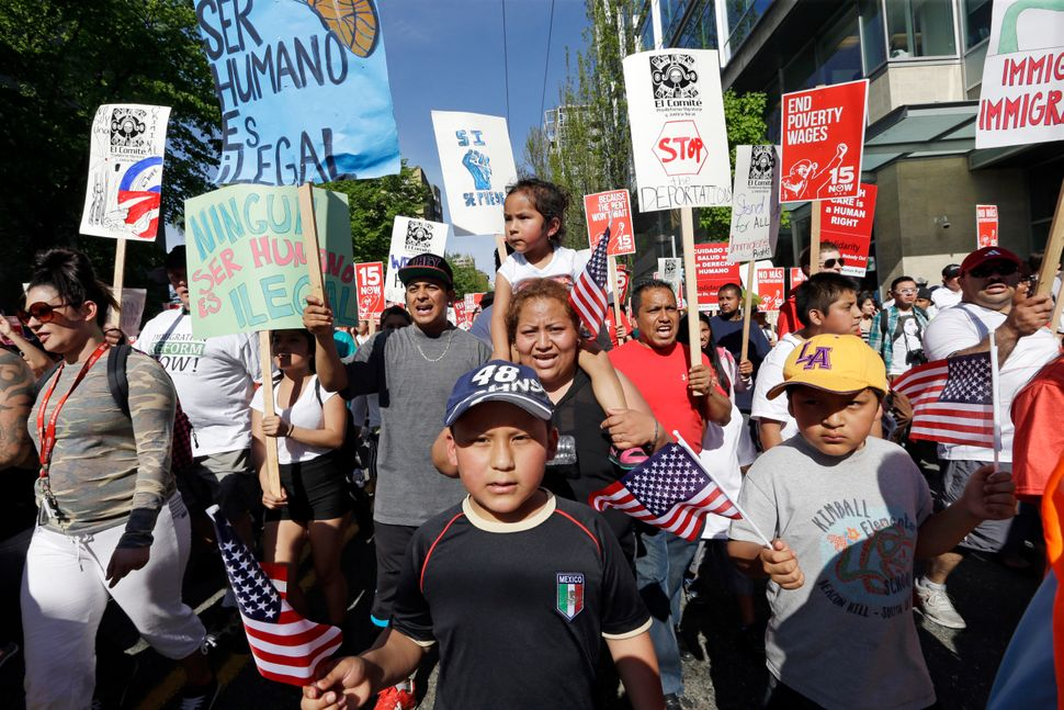 Demonstrators march toward downtown at a May Day march in support of workers rights and a boost in the minimum wage Thursday,